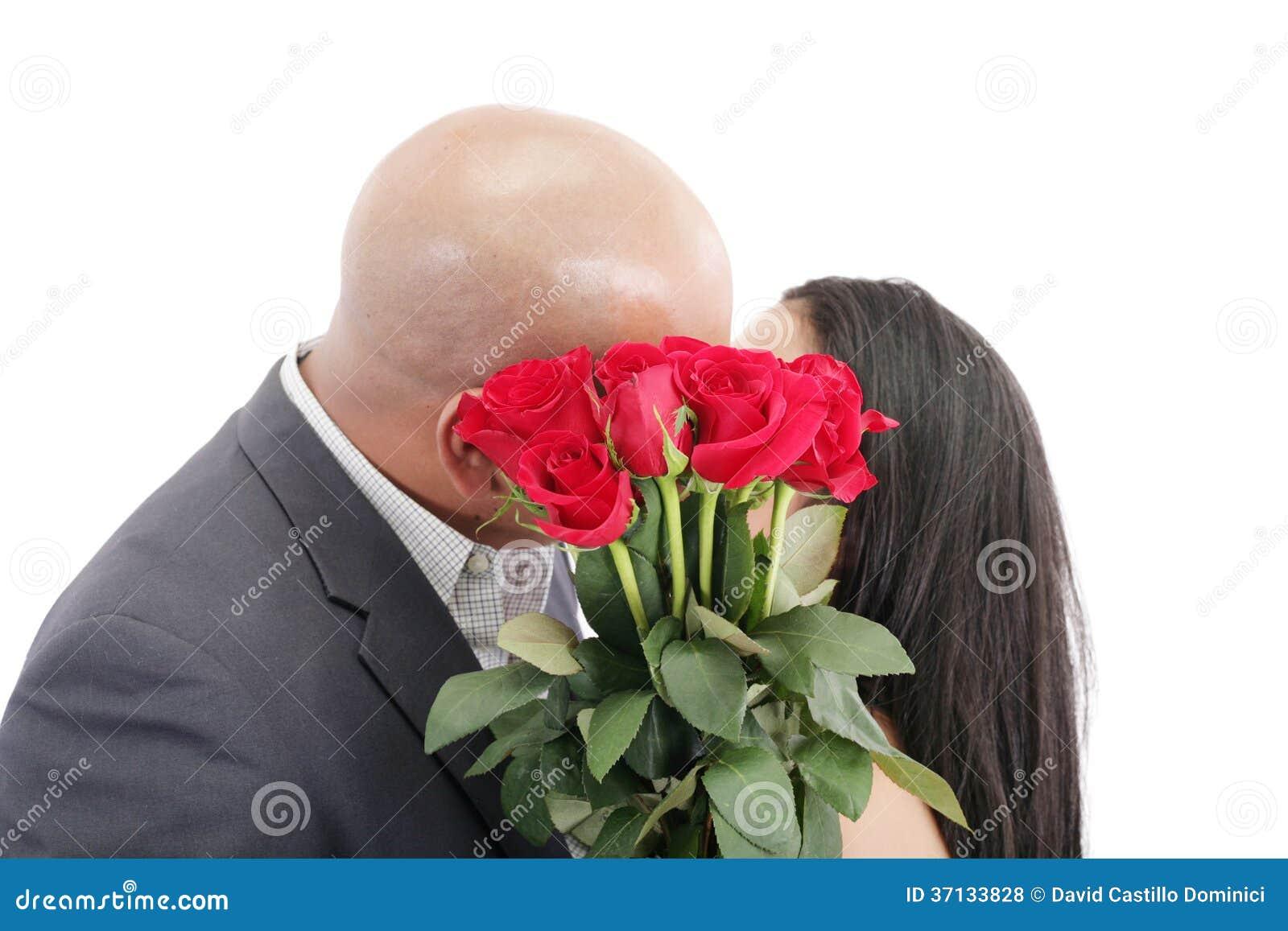 Dos fechas jovenes que se besan detrás de un ramo de rosas rojas