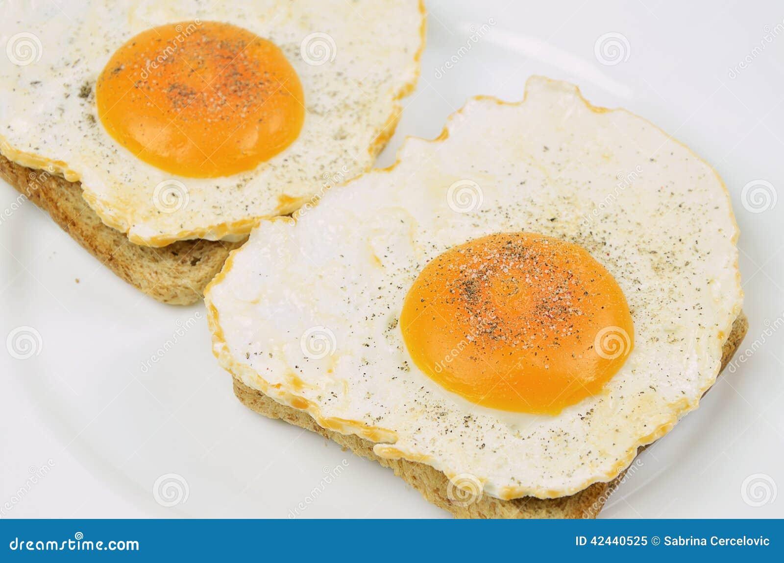 Dos Fried Eggs con la sal y la pimienta en tostada