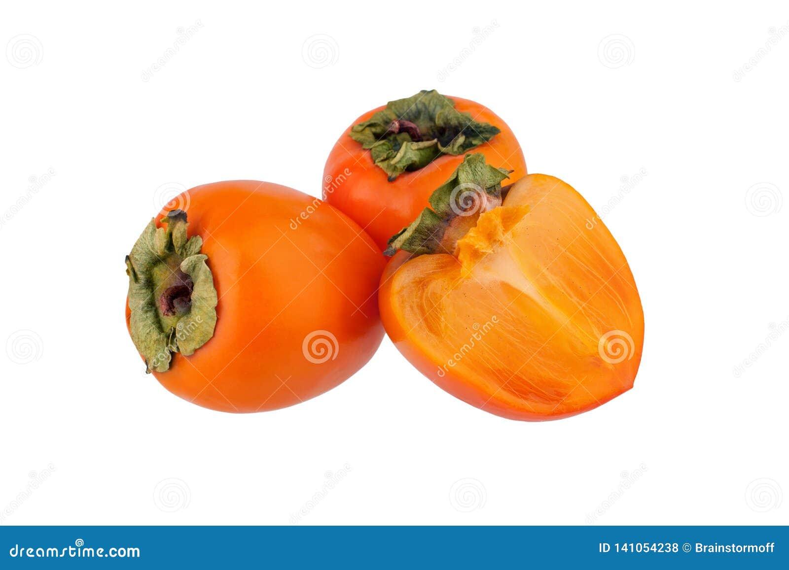 Dos frutas de los caquis o diospyros anaranjados y una mitad cortada del caqui con las hojas verdes en el primer aislado fondo bl