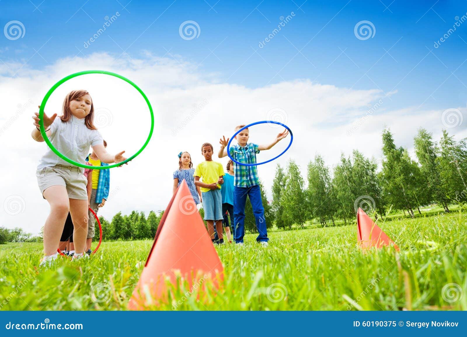 Dos grupos de niños que juegan con los aros del hula