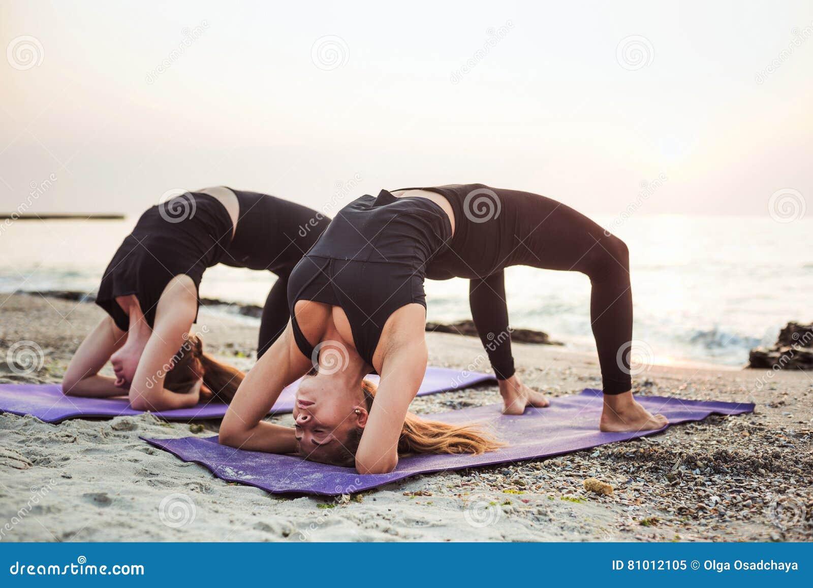 Dos hembras caucásicas jovenes que practican yoga en la playa