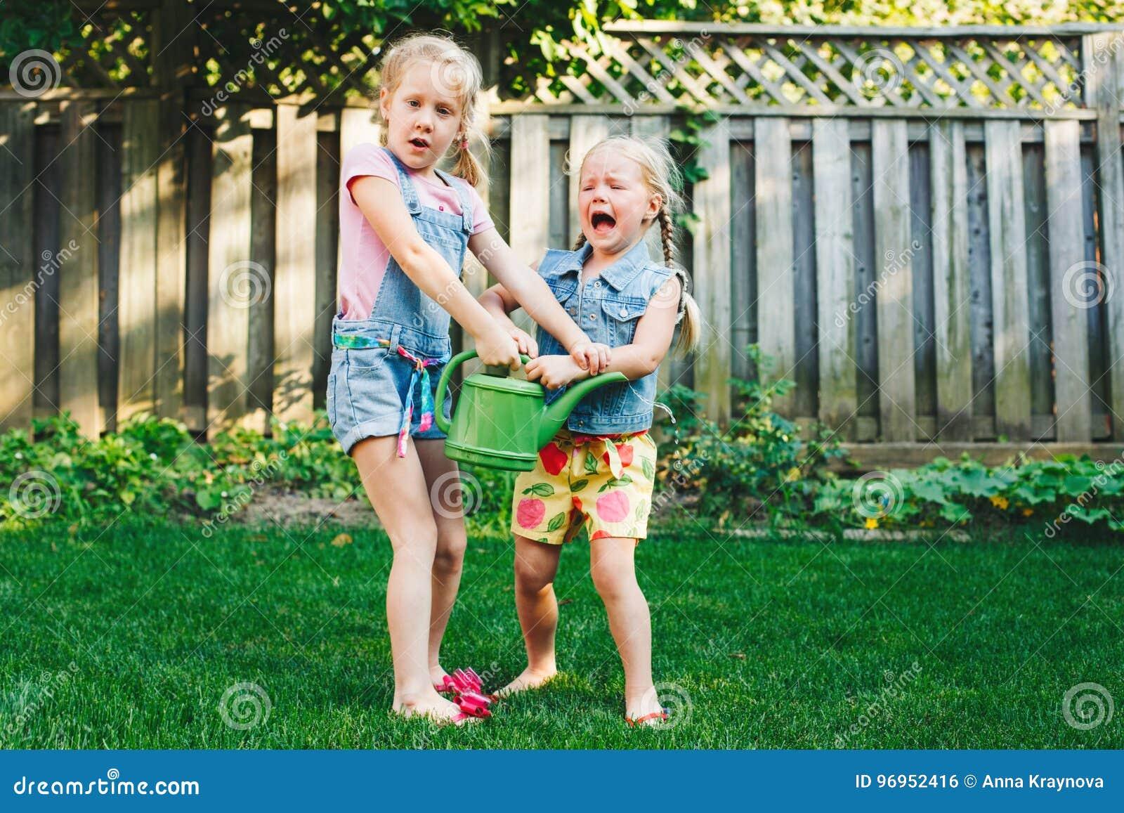 Dos hermanas de las niñas que tienen lucha en el patio trasero casero