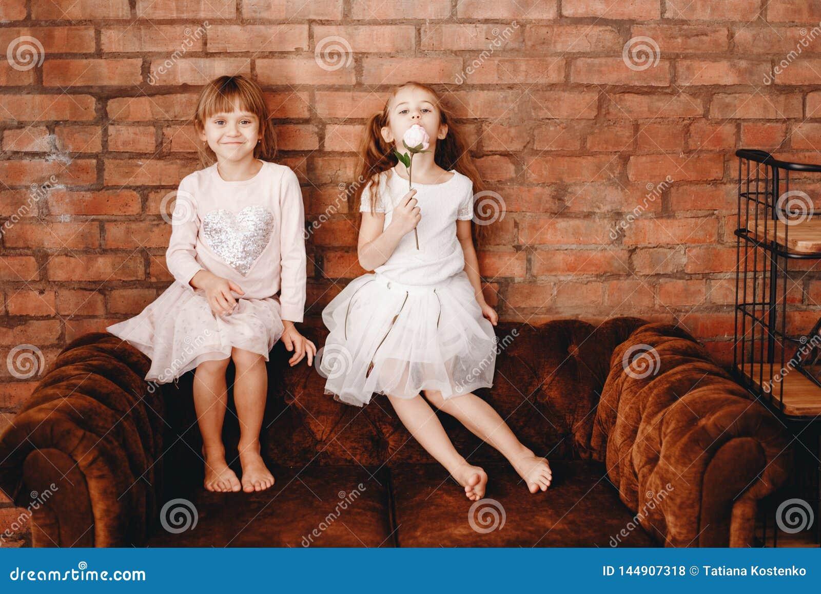 Dos hermanas encantadoras vestidas en vestidos hermosos se están sentando en la butaca marrón en el fondo de una pared de ladri
