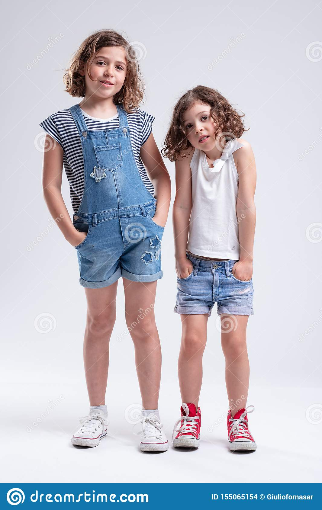 Dos hermanas jovenes que se colocan con las manos en bolsillos