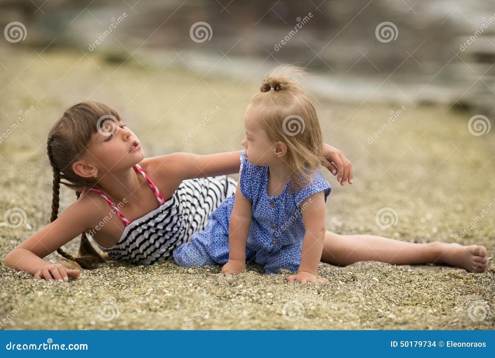 Dos hermanas que juegan en la playa
