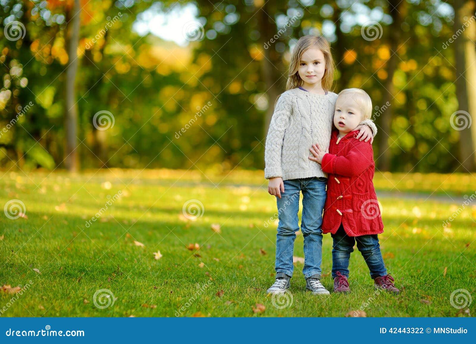Dos hermanas que se divierten en parque hermoso del otoño