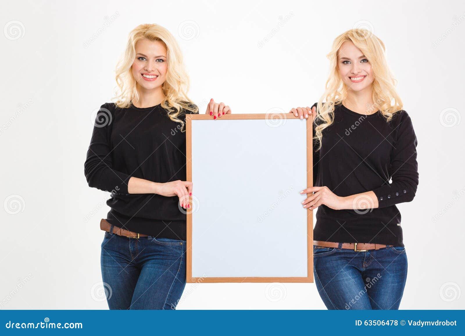 Dos hermanas rubias bastante jovenes hermanan llevar a cabo al tablero en blanco