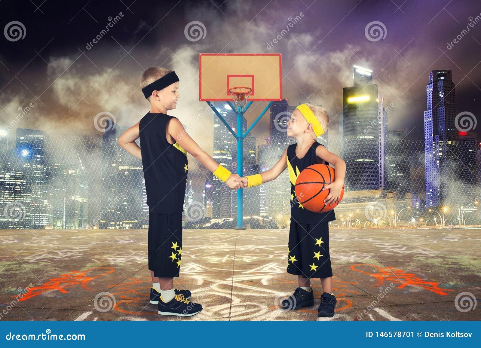 Dos hermanos que juegan a baloncesto en la calle