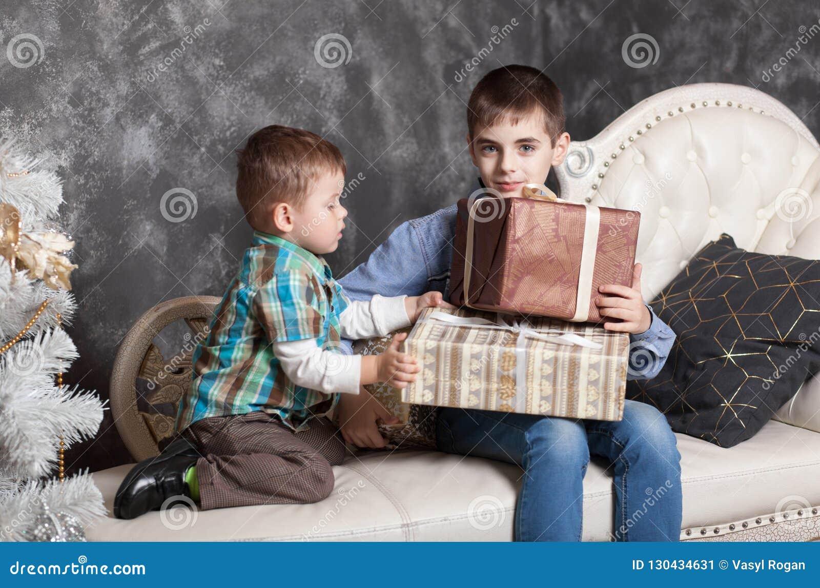 Dos hermanos que se sientan en la cama que abre los regalos del Año Nuevo en cajas Navidad