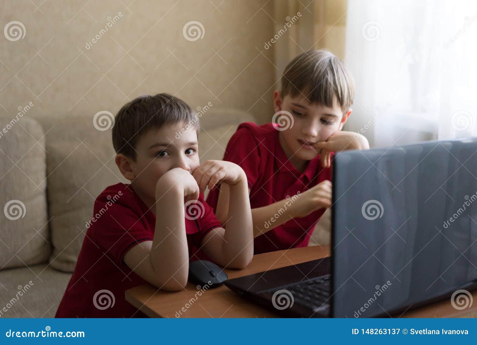 Dos hermanos se están sentando en la sala de estar y están jugando con la PC