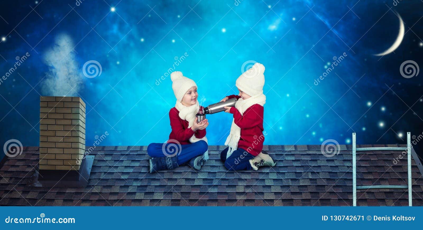 Dos hermanos se sientan el noche de la Navidad en el tejado y beben té caliente de una botella de termo ¡Feliz Navidad y buenas f