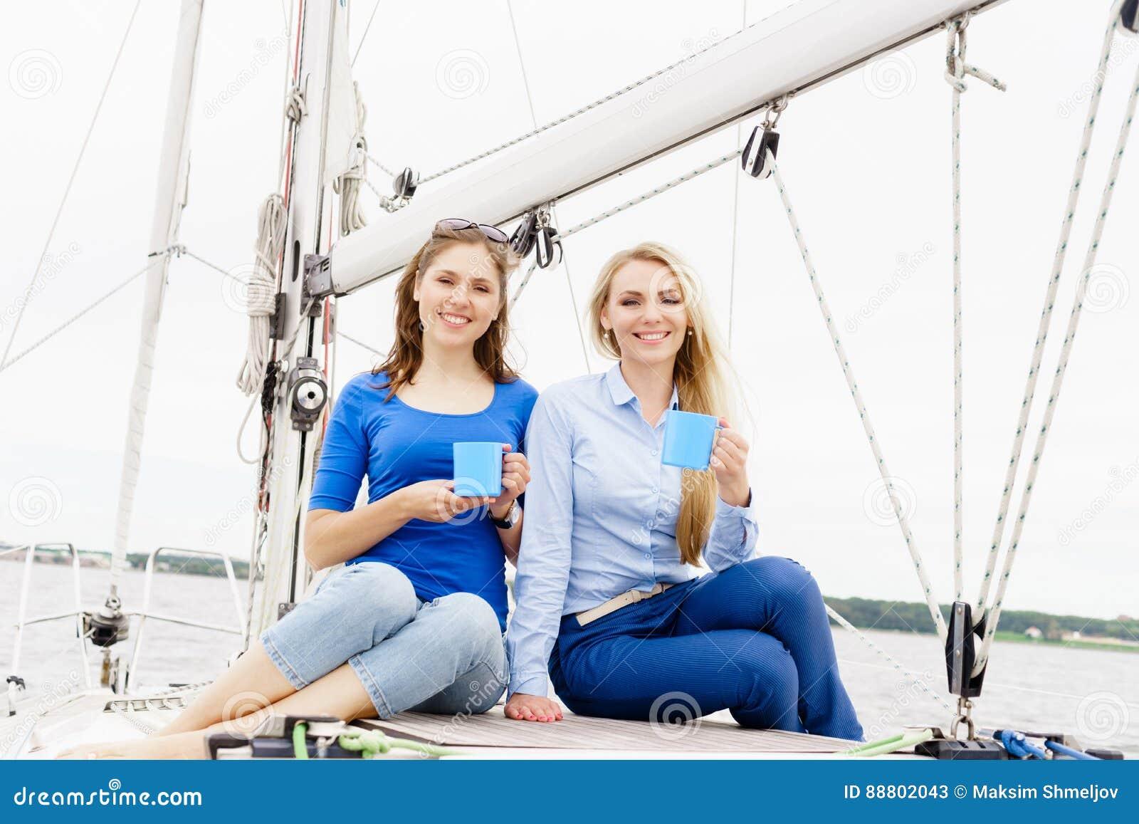 Dos hermosos, chicas jóvenes atractivas que beben el café en un yate