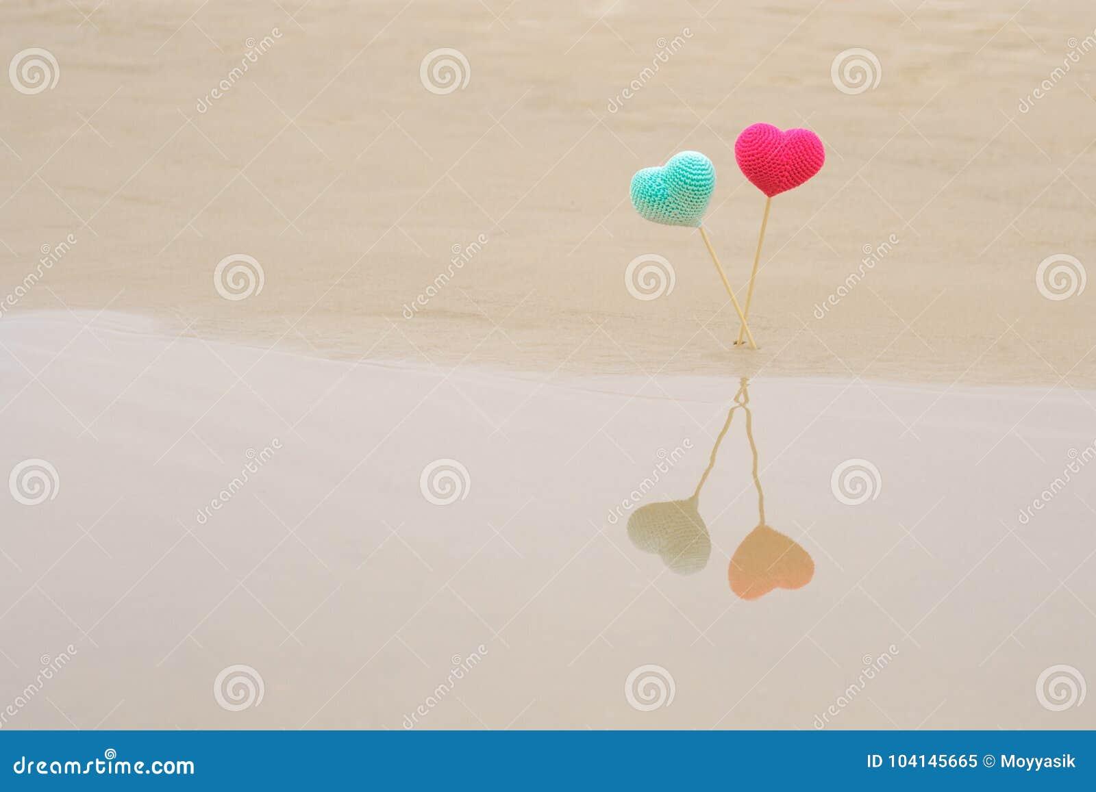 Dos hicieron a ganchillo corazones brillantes y coloridos en los palillos de madera en la playa, reflejada en agua Corazones rosa
