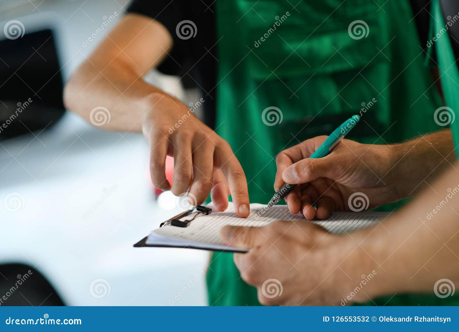 Dos hombres completan los documentos del servicio del coche
