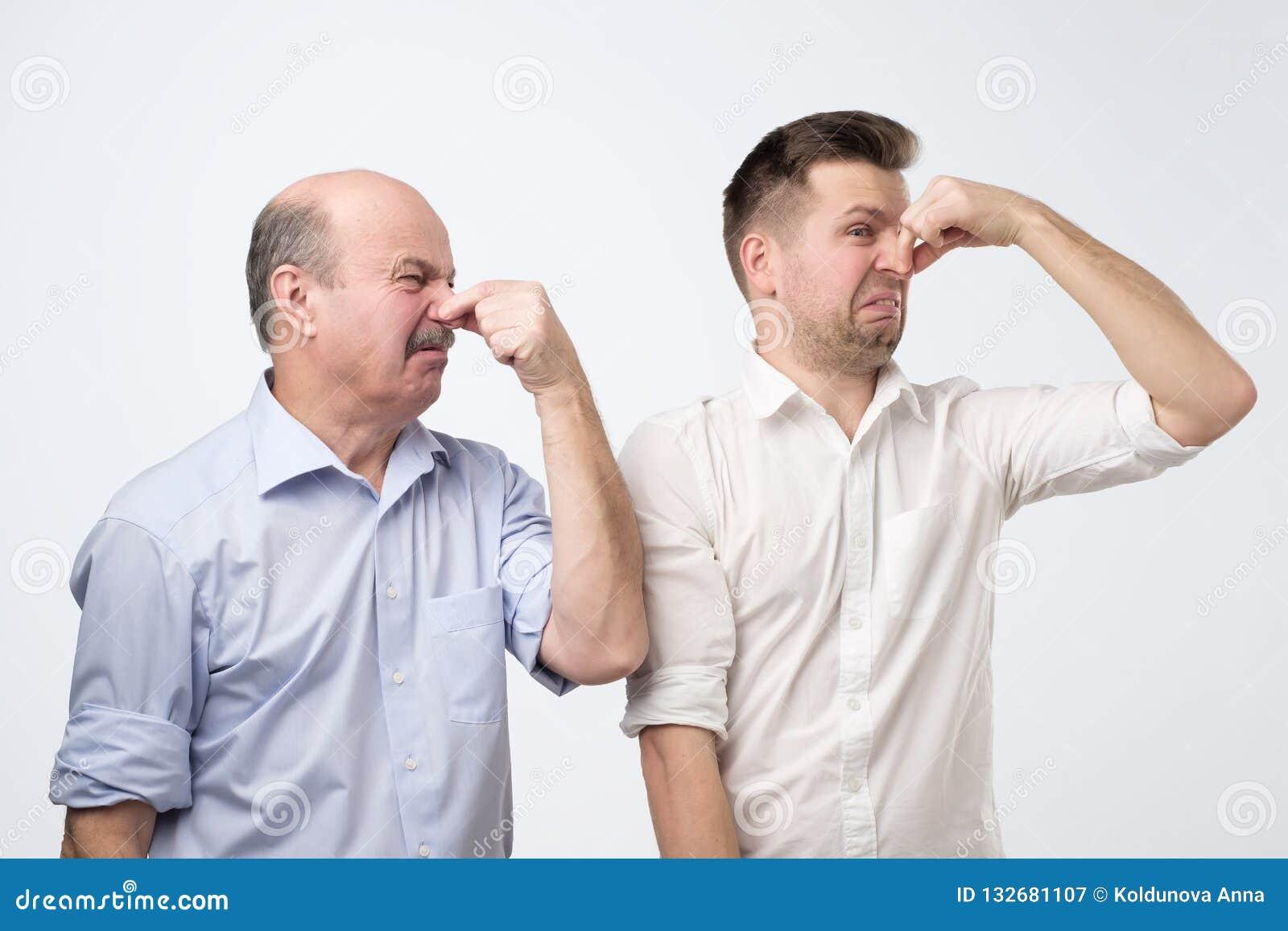Dos hombres cubren sus narices debido a un mún olor
