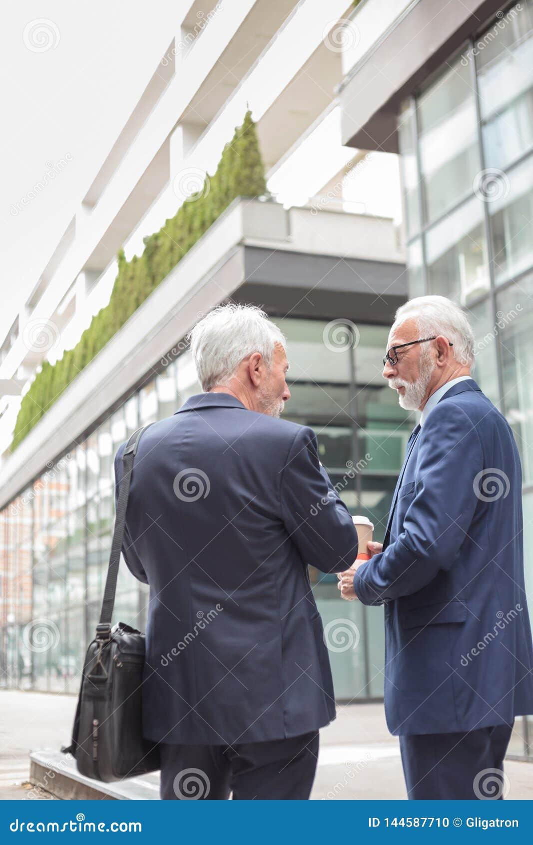 Dos hombres de negocios cabelludos grises mayores que caminan abajo de la calle y que hablan, vista posterior