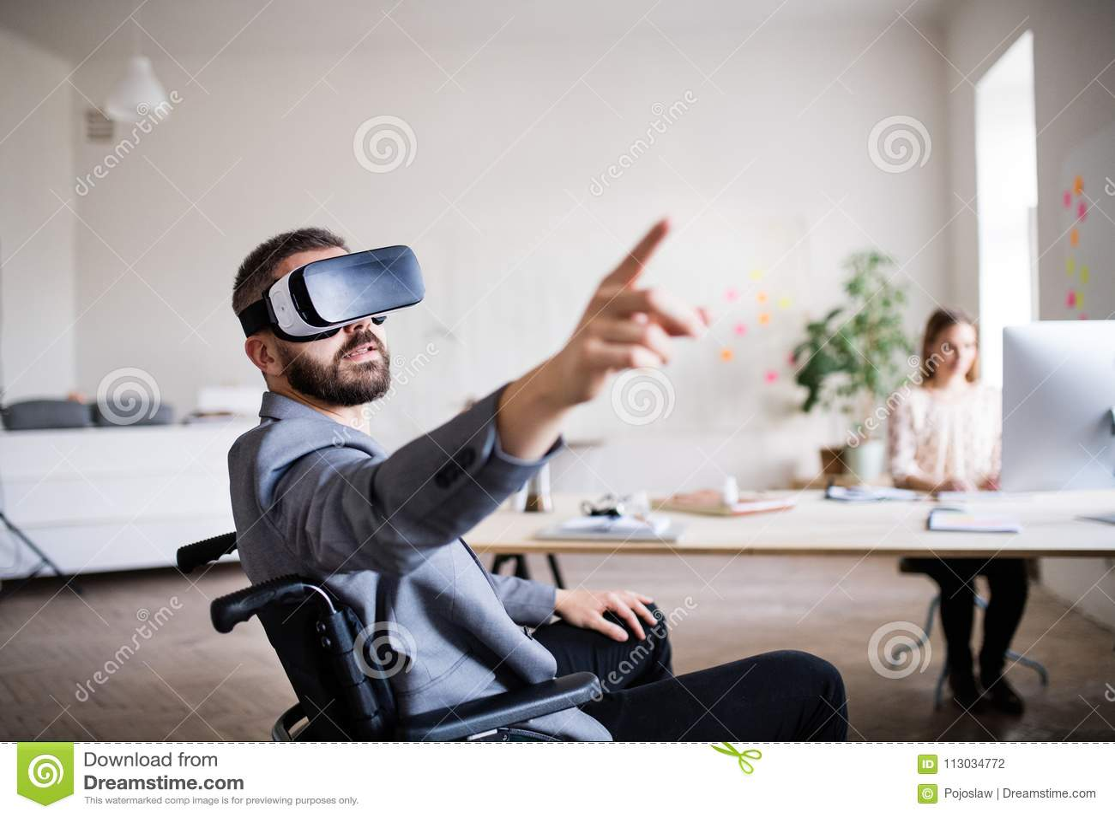 Dos hombres de negocios con la silla de ruedas y gafas de VR en la oficina