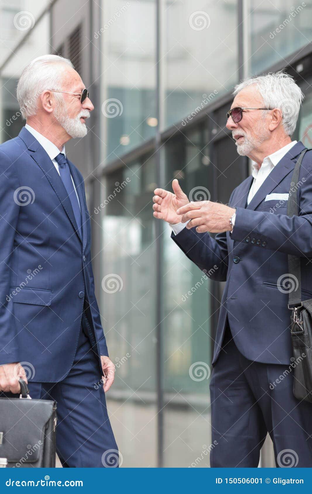 Dos hombres de negocios grises mayores del pelo que hablan en la calle