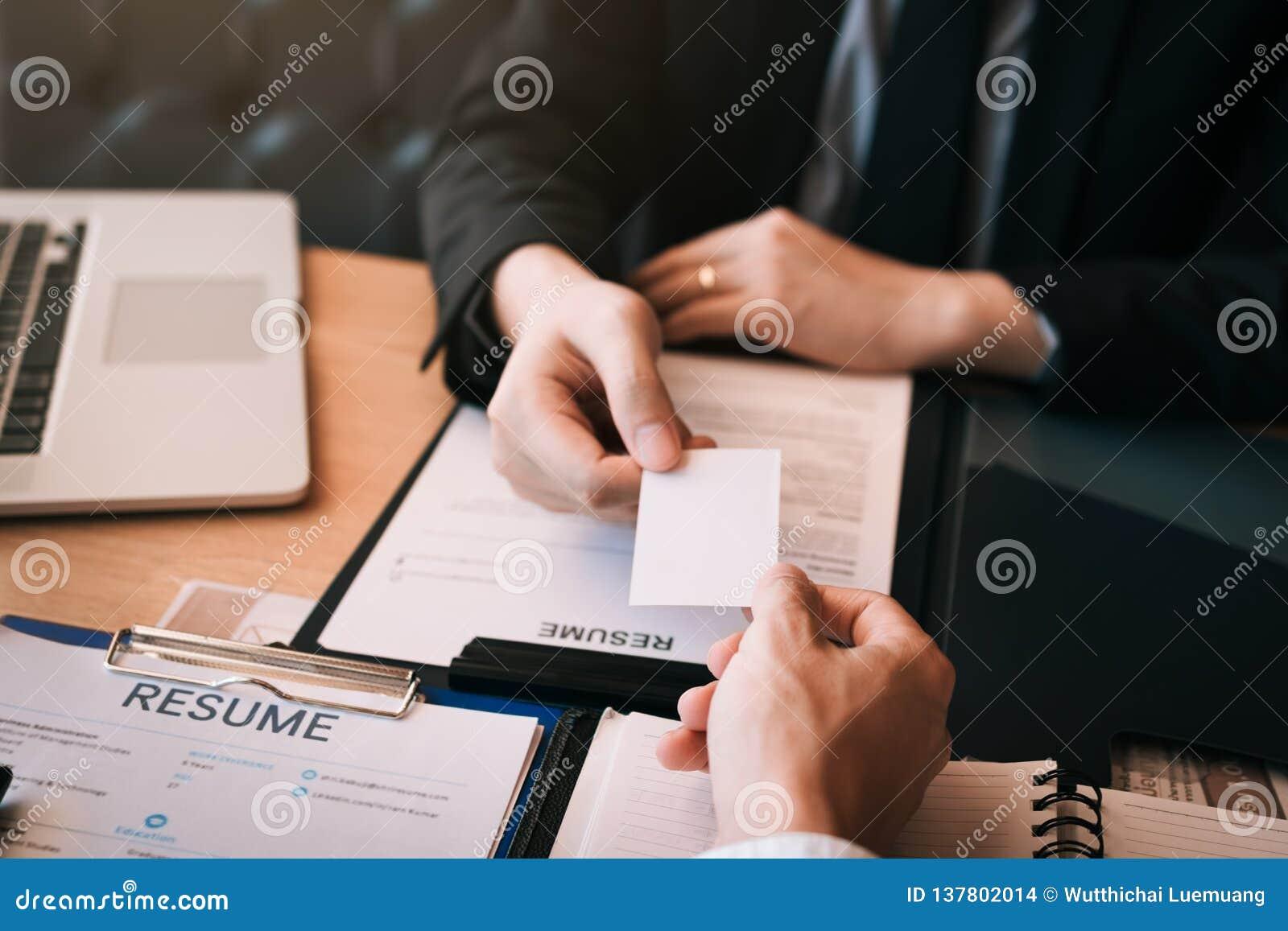 Dos hombres de negocios intercambiaron las tarjetas de visita blancas en una tabla de madera en oficina