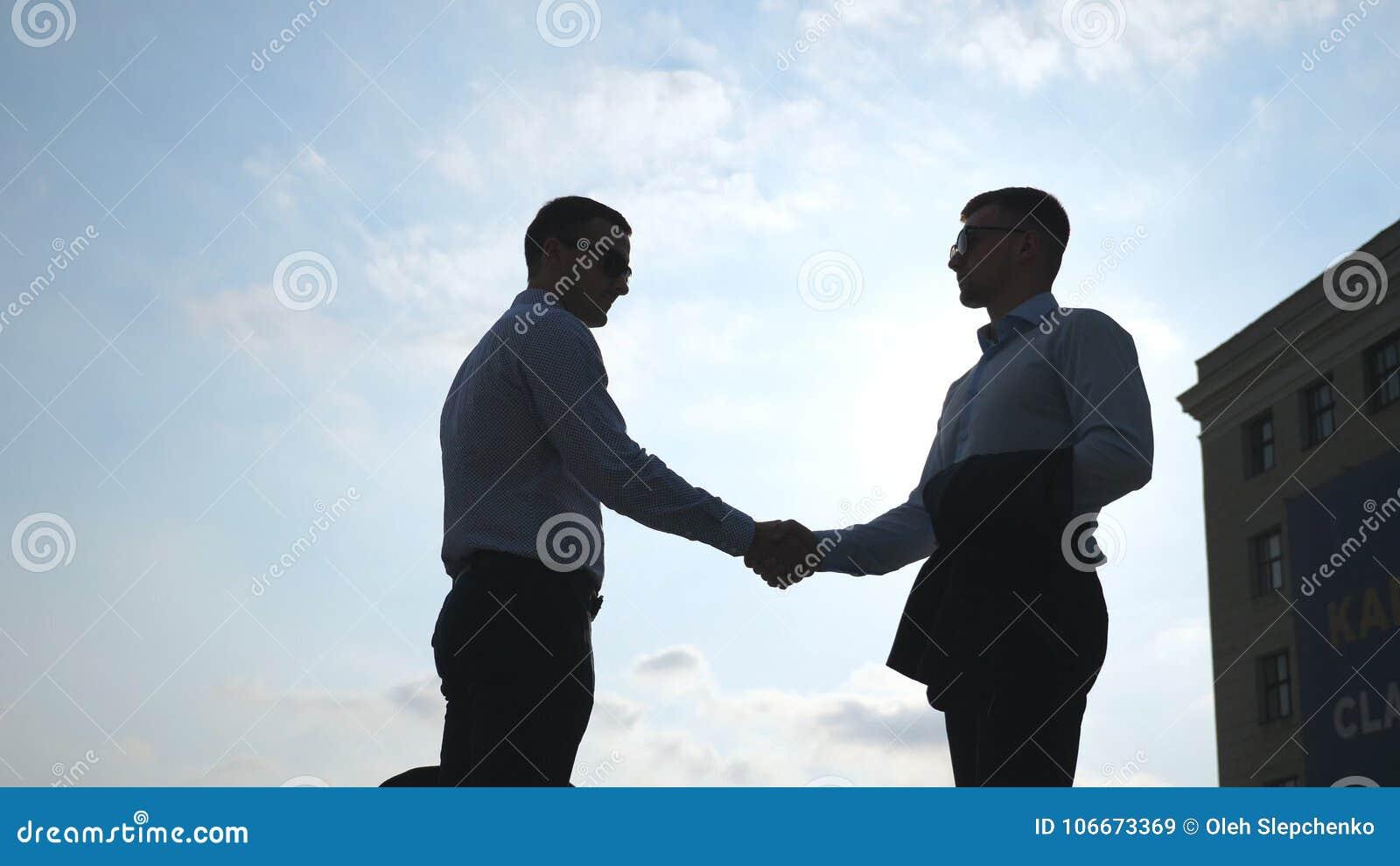 Dos hombres de negocios jovenes que se encuentran en la ciudad y que se saludan Los colegas sacuden las manos al aire libre Mano