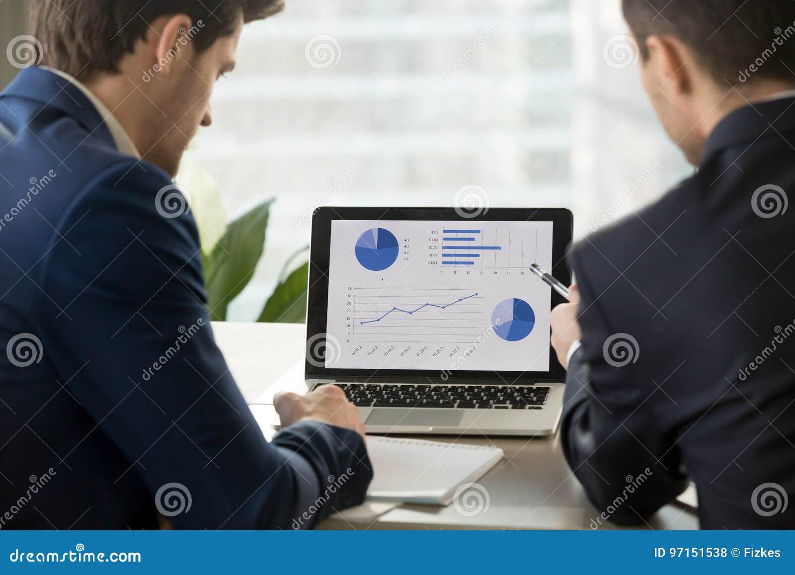 Dos hombres de negocios que analizan el stats en el ordenador portátil, programas informáticos de contabilidad,