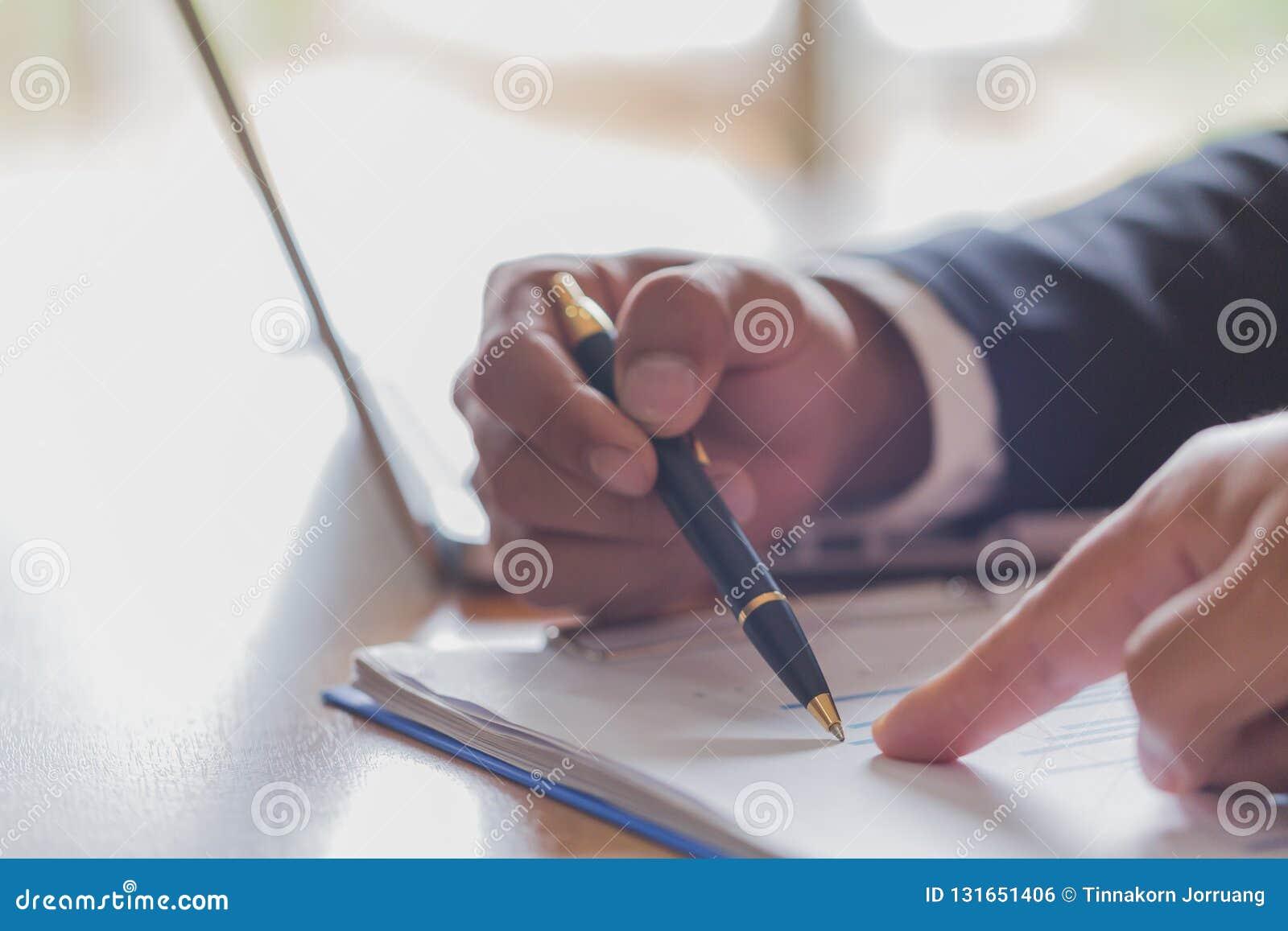 Dos hombres de negocios que analizan los datos financieros del stats, señalando en la pantalla con el gráfico y las cartas de lev
