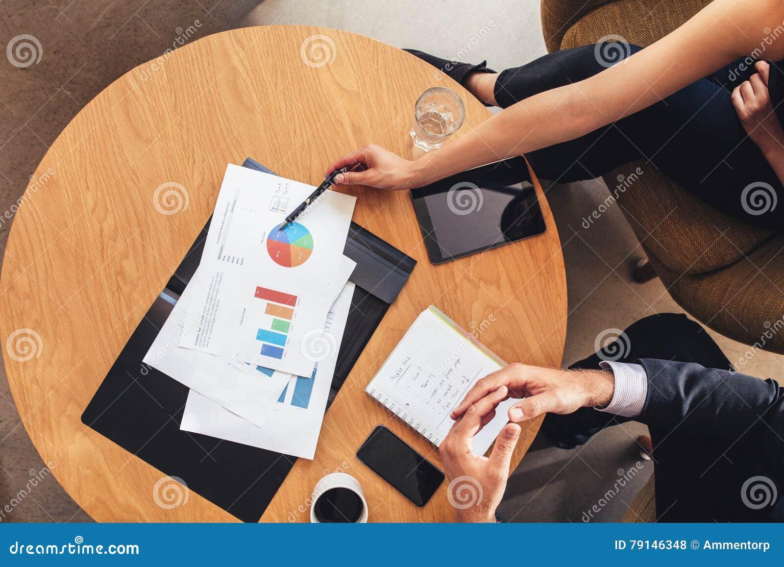 Dos hombres de negocios que trabajan con las cartas alrededor de la tabla
