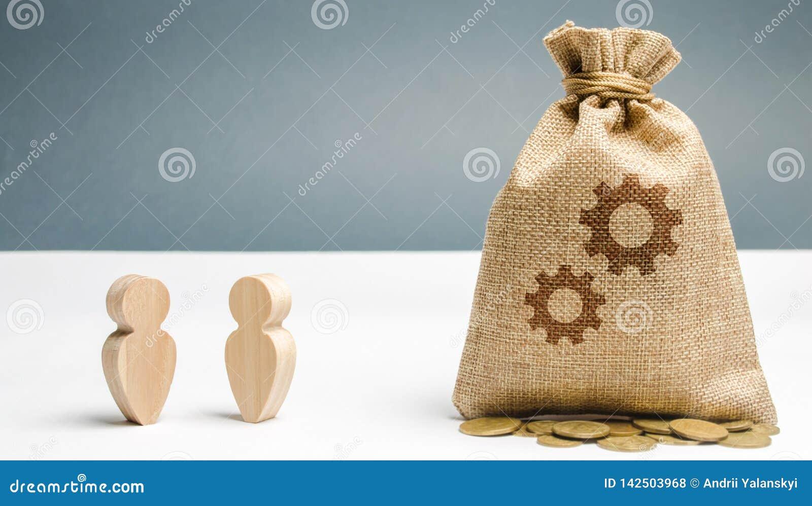Dos hombres de negocios se est?n colocando cerca del bolso con la imagen de engranajes El proceso de aprender a un nuevo empleado