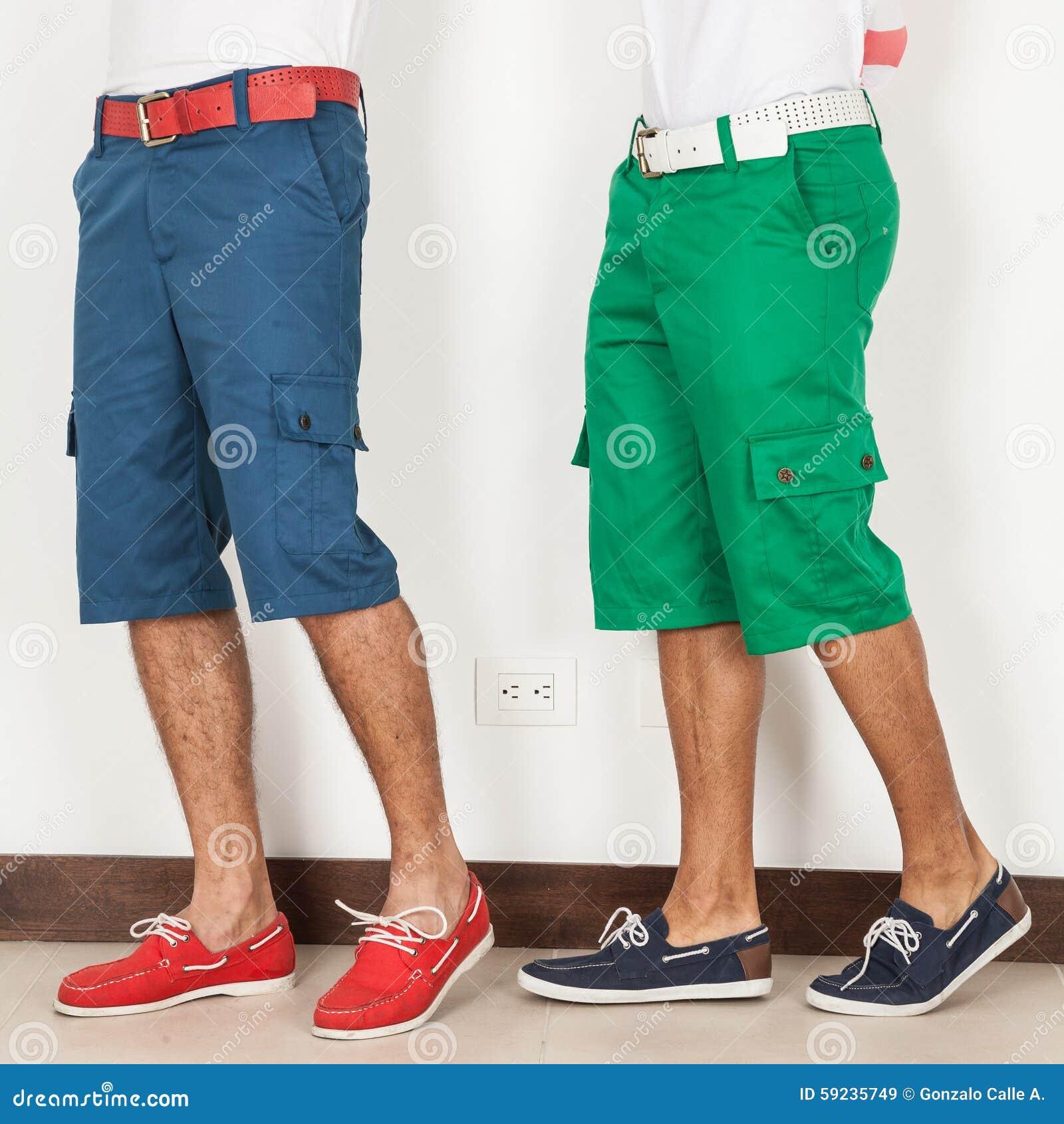Download Dos Hombres En Los Pantalones Cortos Verdes Y Los Colores Azules En El Fondo Blanco Imagen de archivo - Imagen de fresco, azul: 59235749