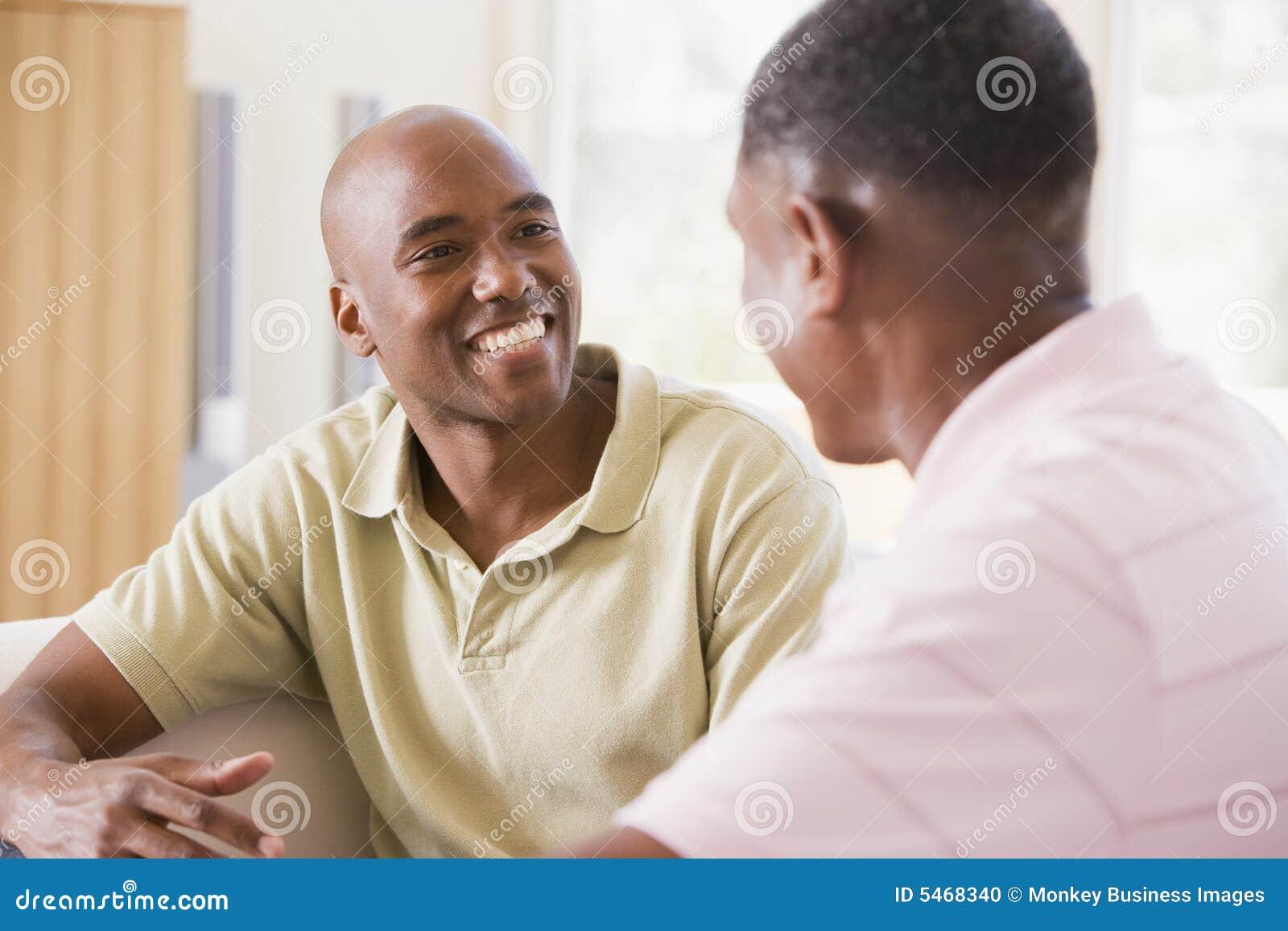 Dos hombres en sala de estar que hablan y que sonríen