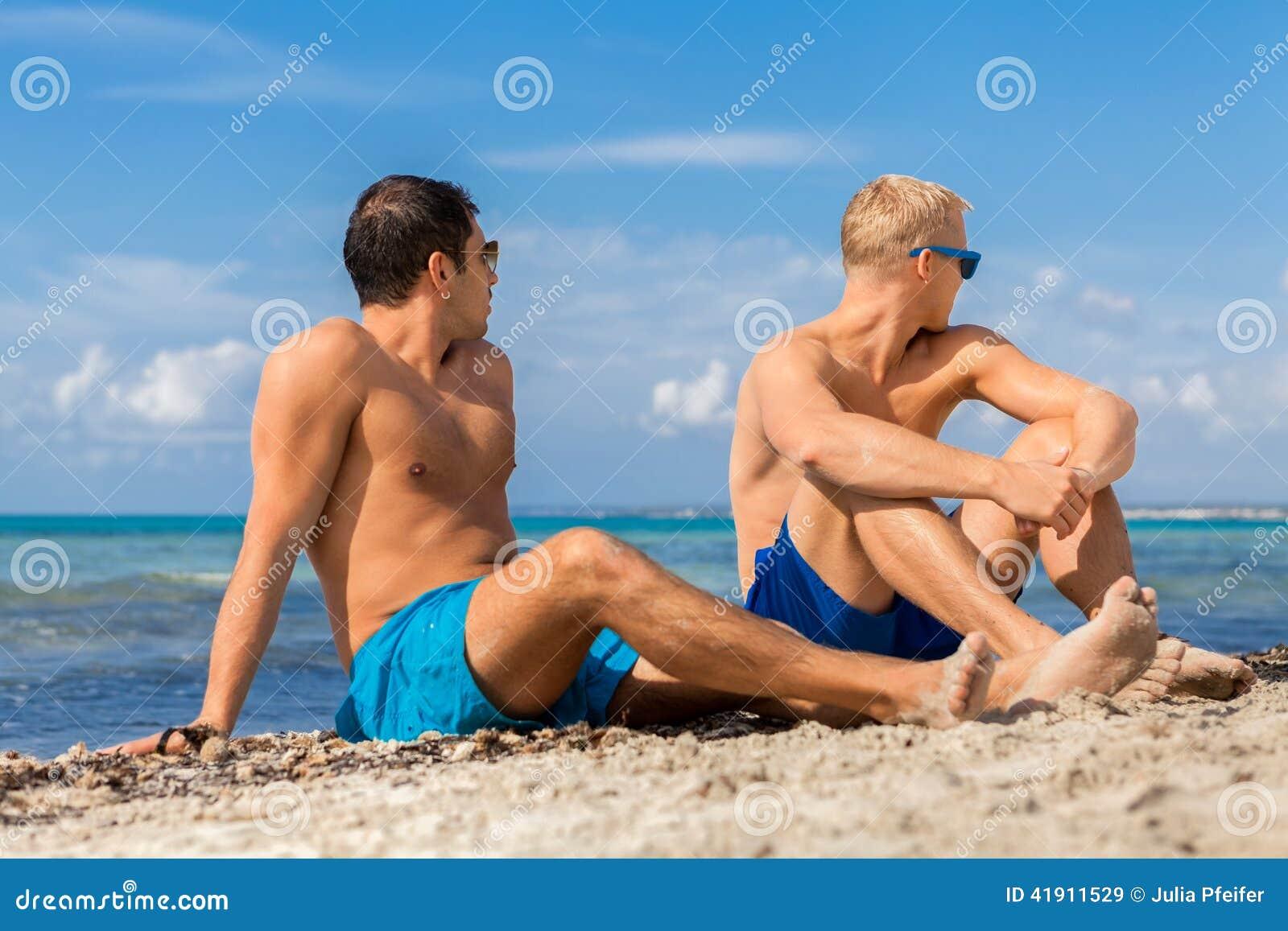 Dos hombres jovenes hermosos que charlan en una playa