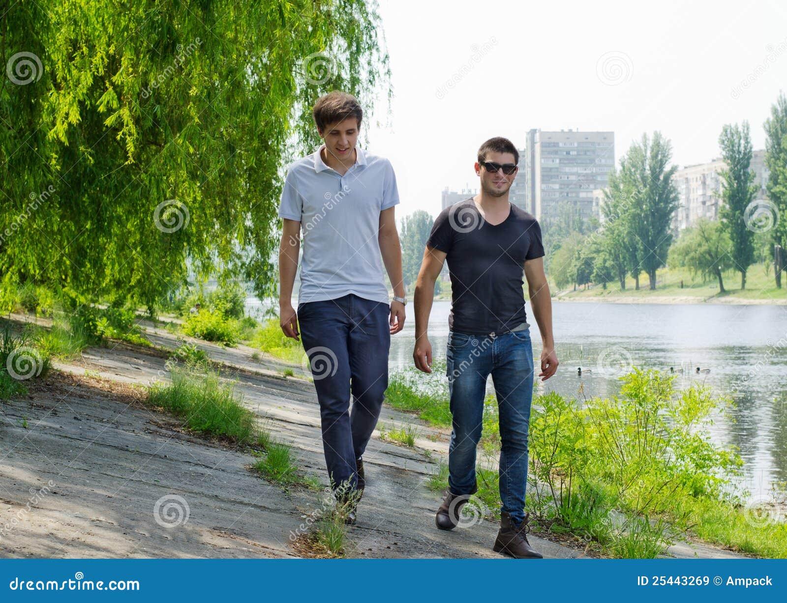 Dos hombres jovenes que recorren a lo largo de un riverbank