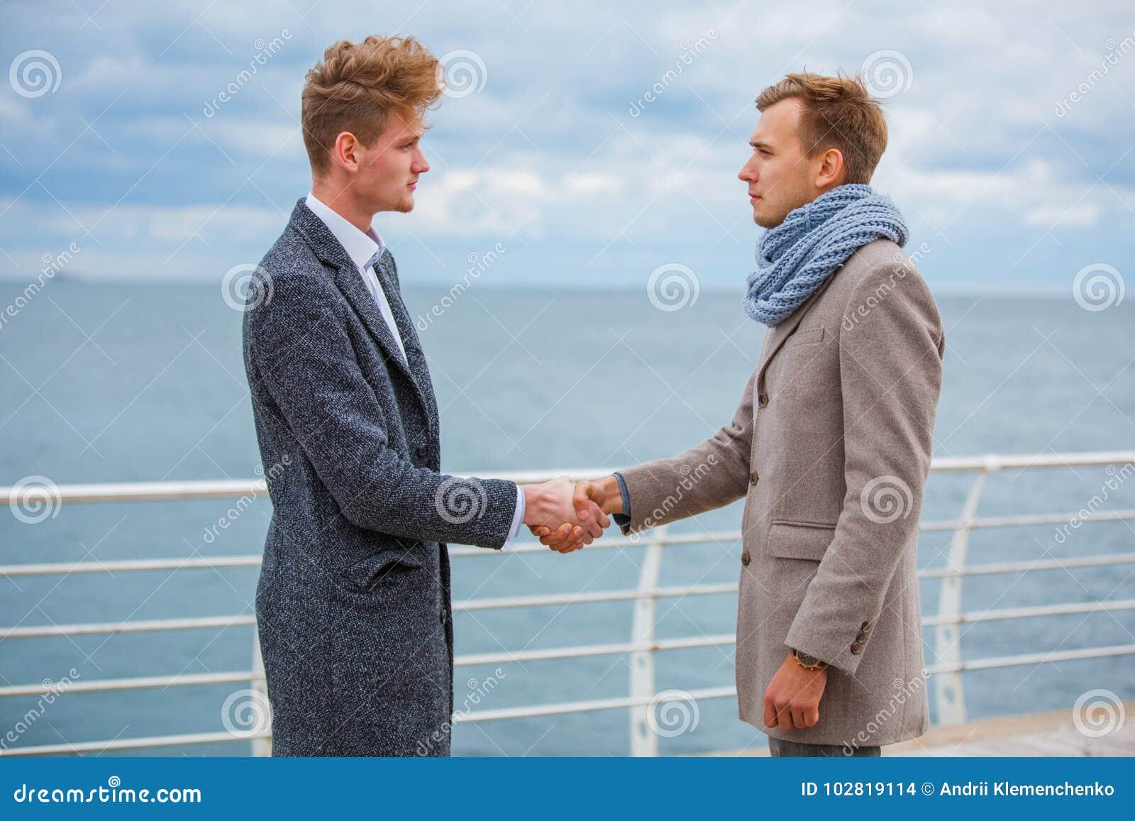 b0dadc901 Dos Hombres Jovenes Que Sacuden Las Manos Al Aire Libre Cerca Del ...