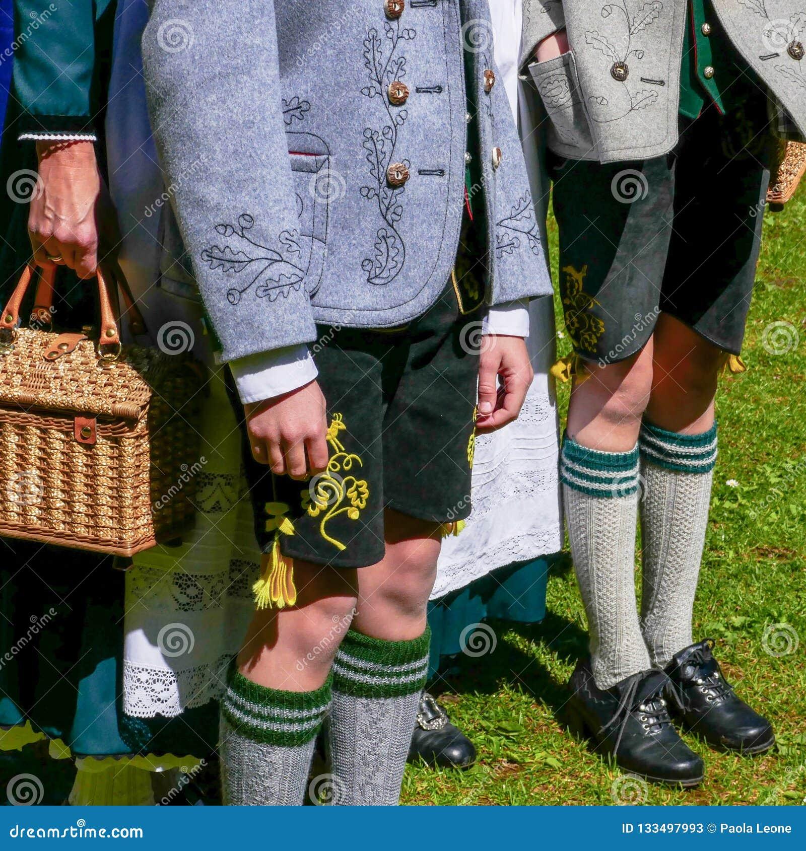 Dos hombres jovenes y una mujer que lleva la ropa bávara tradicional alemana, colocándose en un día soleado ningunas caras