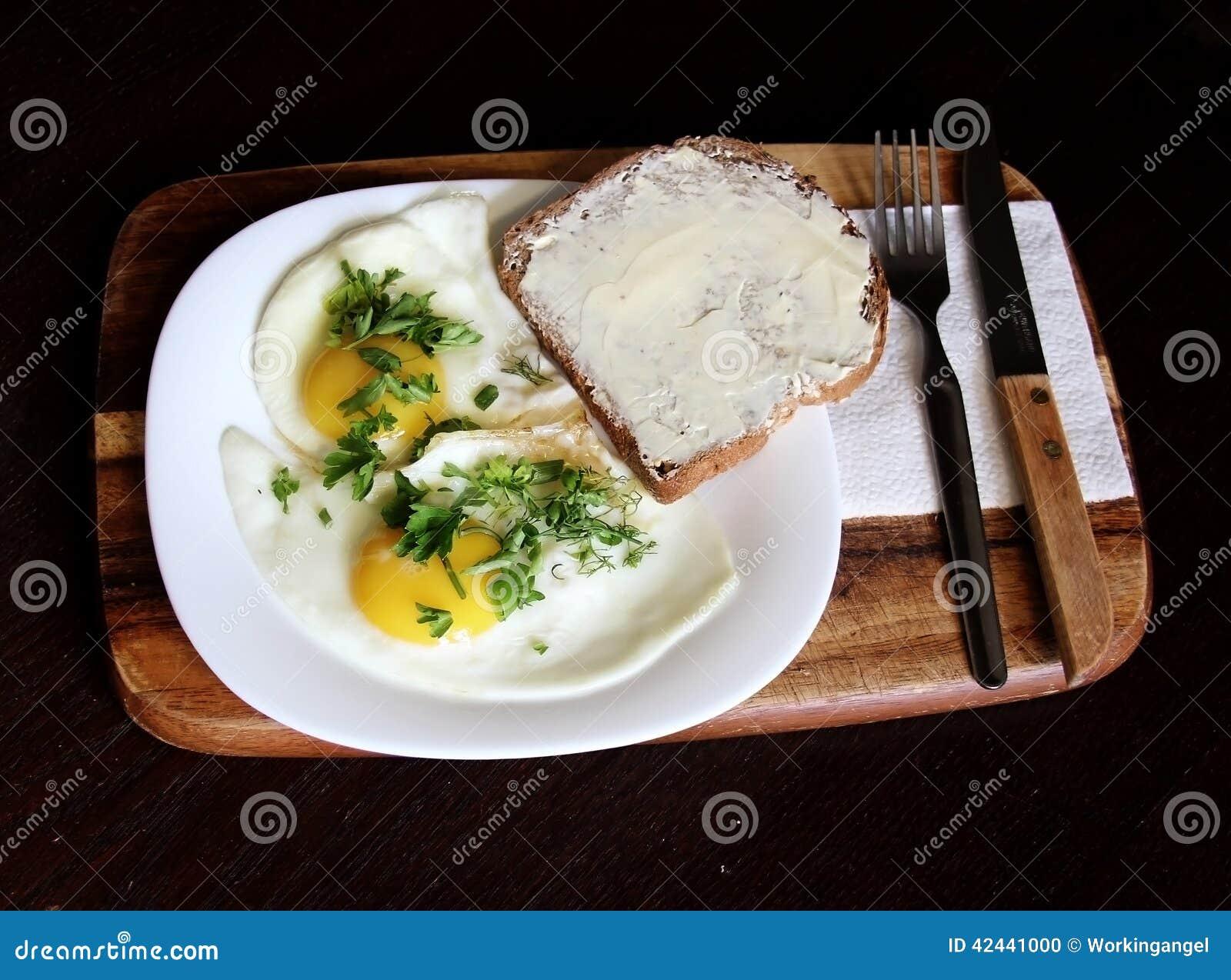 Dos huevos fritos con pan y mantequilla y perejil cortado