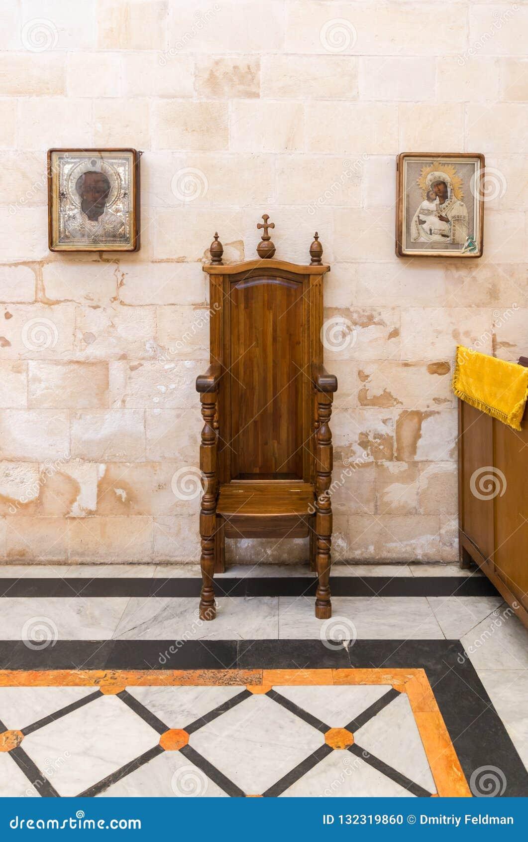 Dos iconos cuelgan en la pared en los lados del trono de madera decorativo en la iglesia de Alexander Nevsky en Jerusalén, Israel