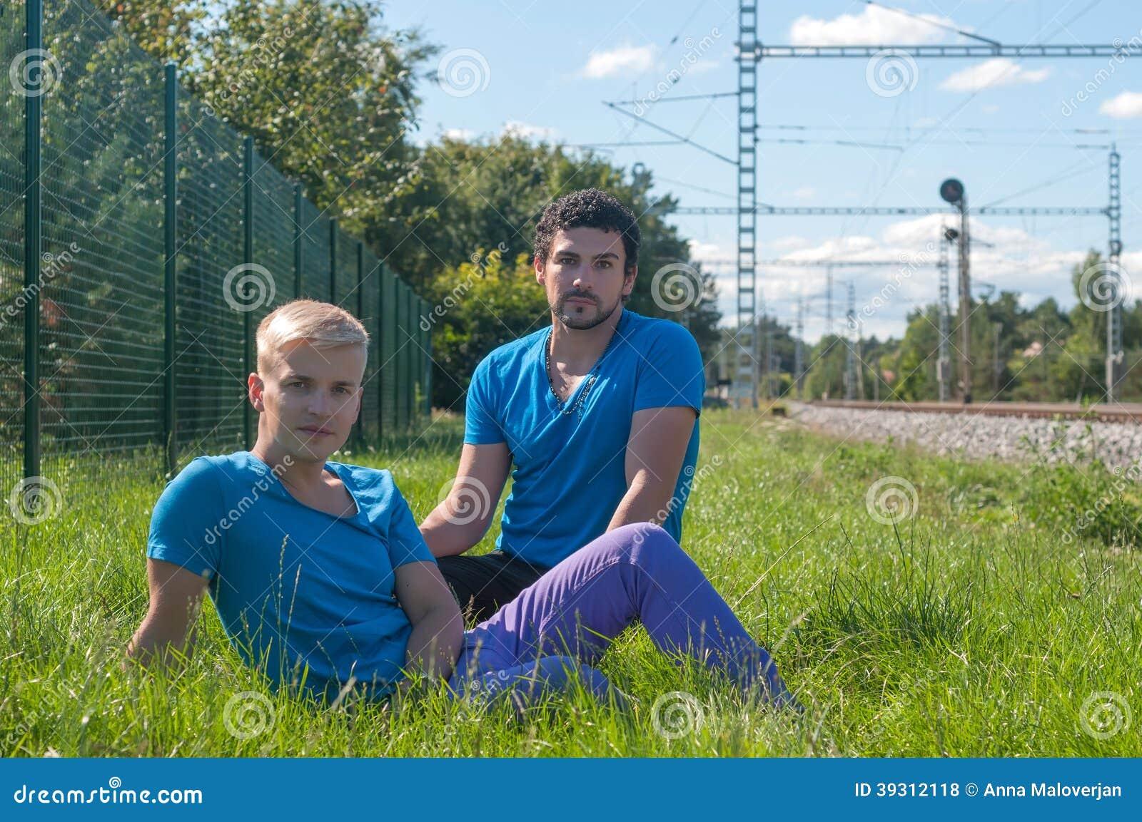 Dos individuos que se sientan en una hierba
