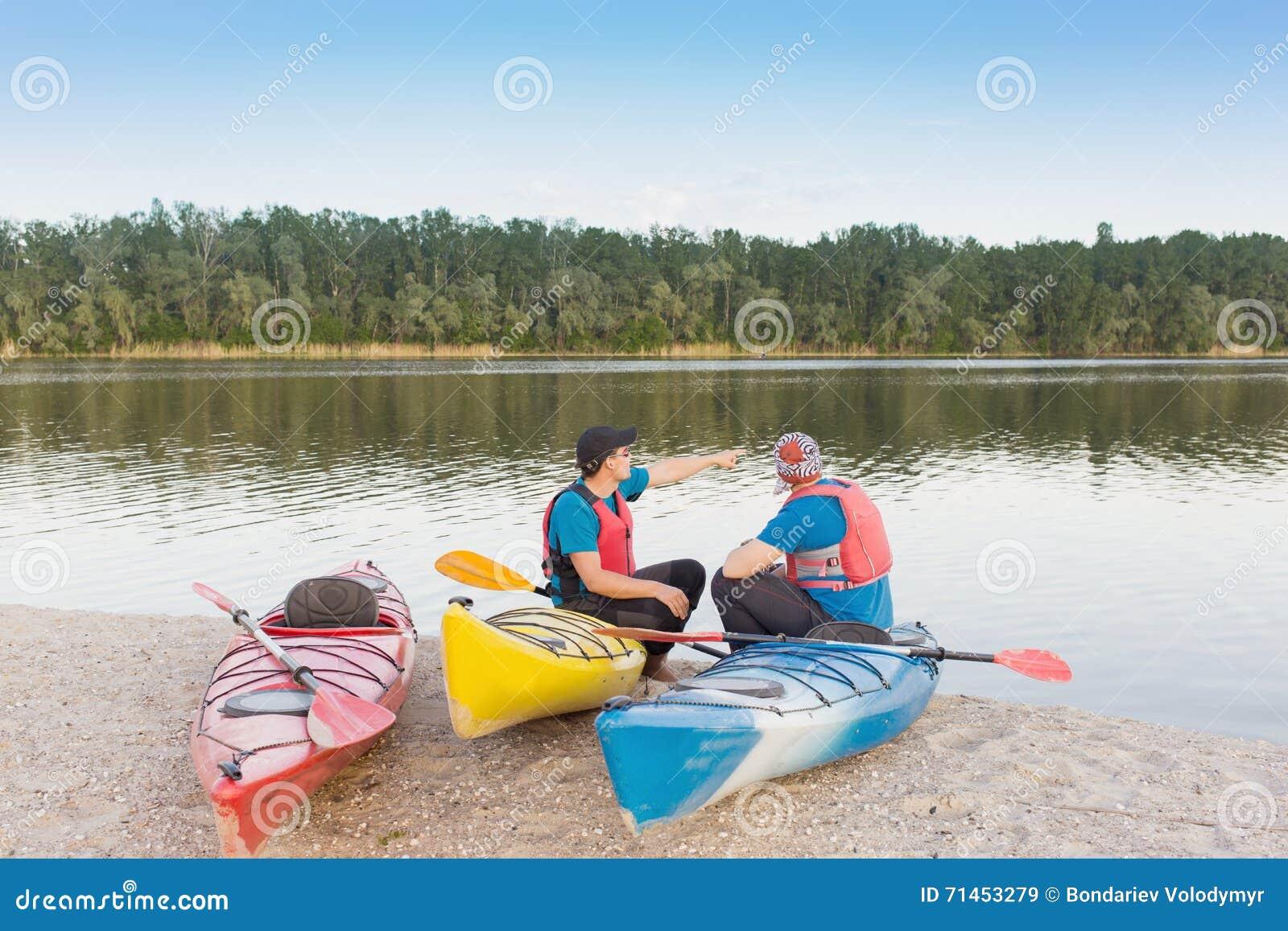 Dos individuos viajan el río en kayaking