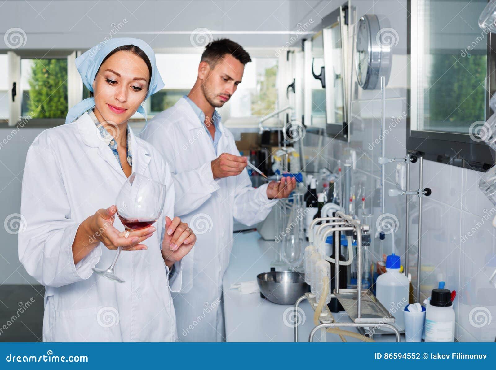 Dos investigadores en la capa blanca que comprueban acidez del vino en laboratorio