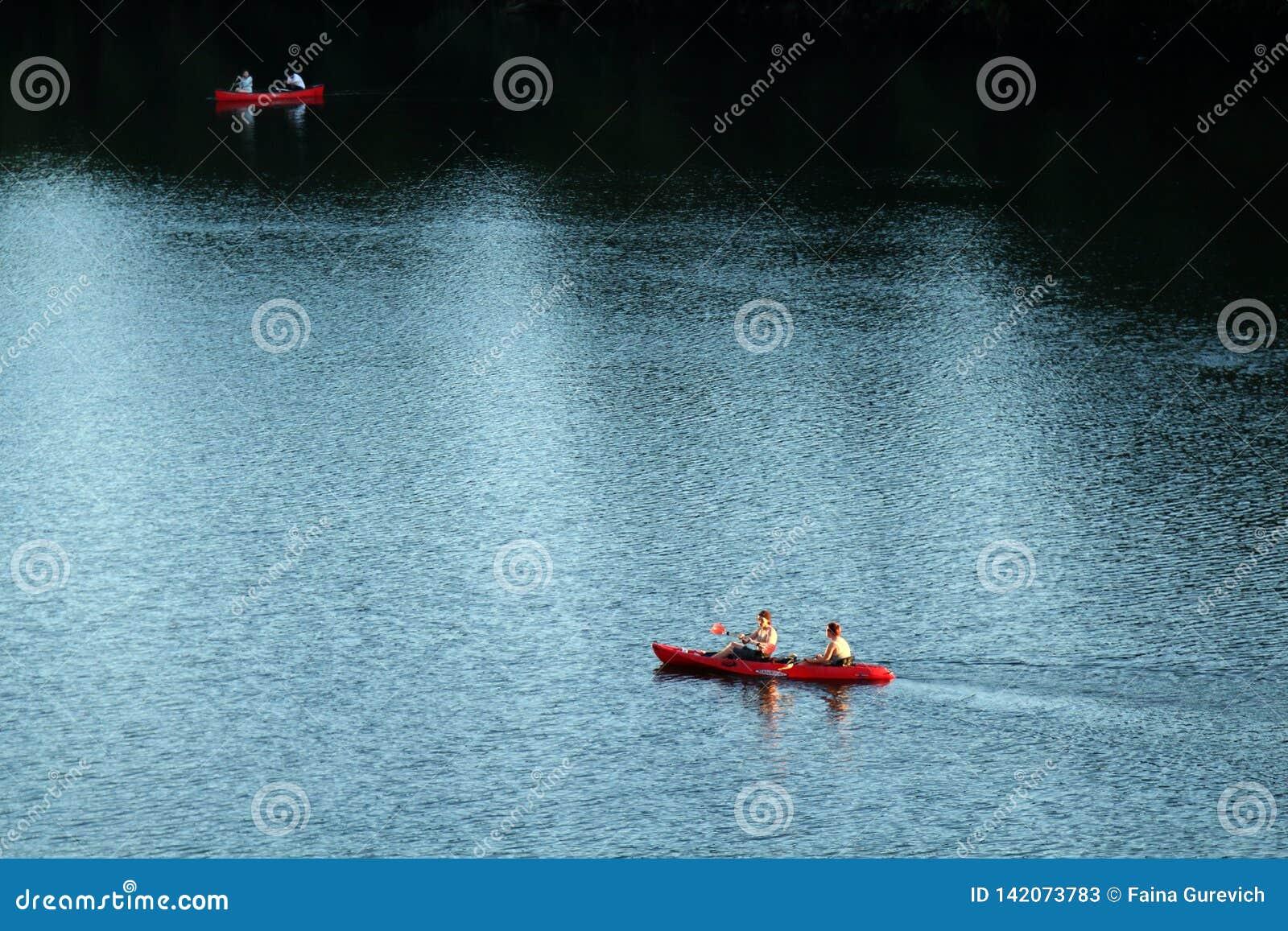 Dos kajaks rojos que navegan las aguas ligeras y oscuras del río Colorado según lo visto del puente del congreso en Austin