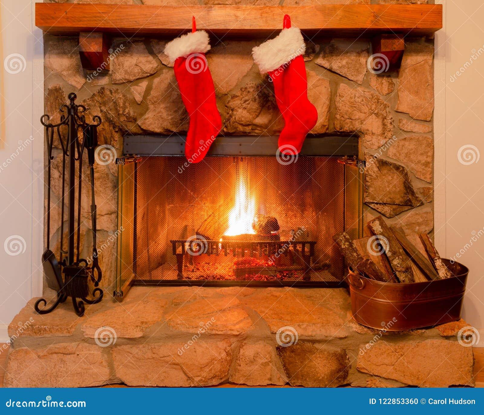 Dos medias de la Navidad en la capa de una chimenea de piedra con un fuego caliente