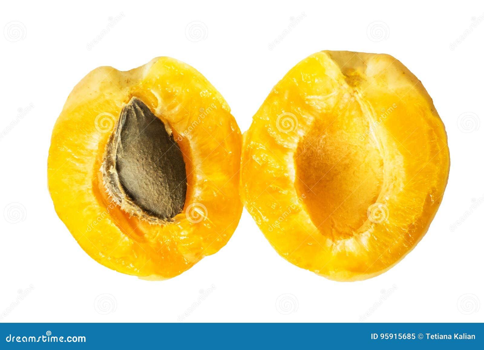 Dos mitades de un albaricoque maduro jugoso de la piña con un hueso dentro Fruta partida en dos aislada en un fondo blanco Visión