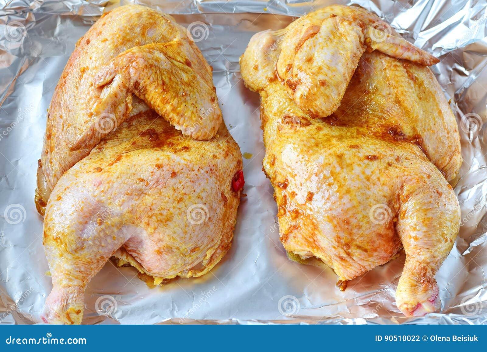 Dos mitades del pollo adobado crudo en una bandeja en un folio antes de ser asada El cocinar paso a paso Consumición sana