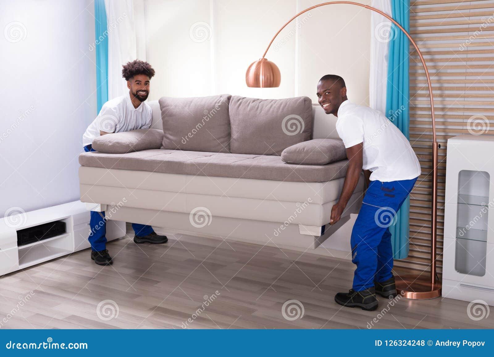 Dos motores masculinos que colocan el sofá