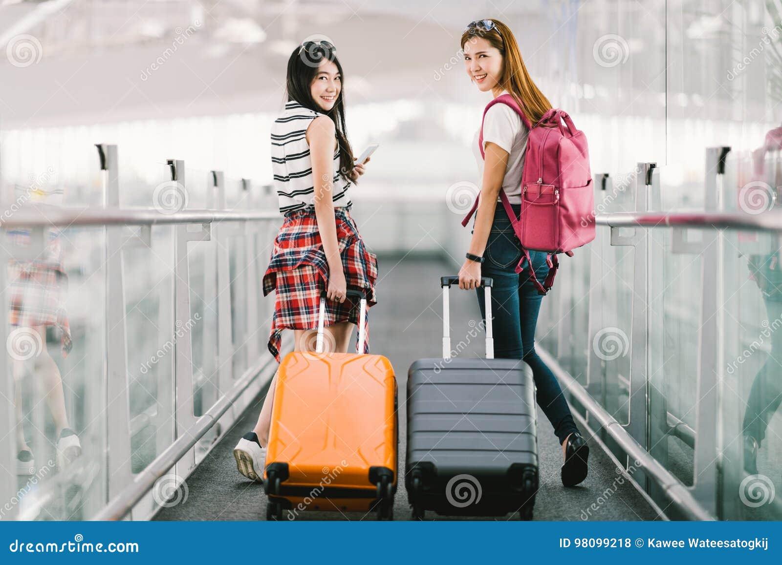 Dos muchachas asiáticas felices que viajan al extranjero junto, equipaje de la maleta que lleva en aeropuerto Transporte aéreo o