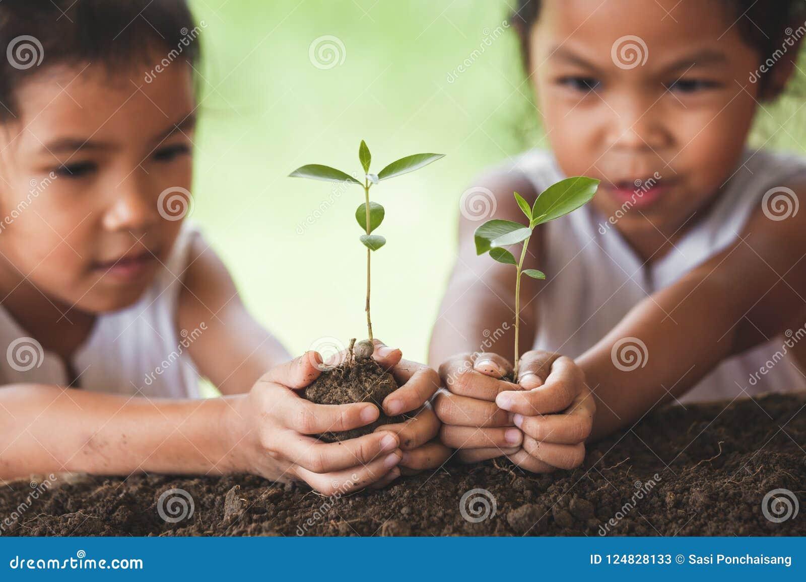 Dos muchachas asiáticas lindas del niño que plantan el árbol joven en suelo negro