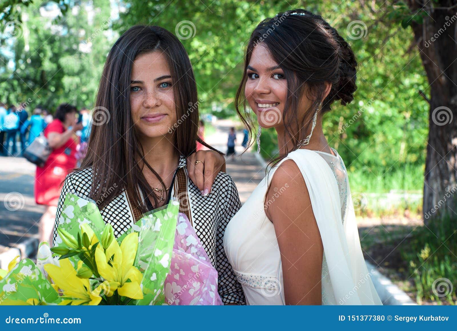 Dos muchachas cerca de un árbol El retrato de una señora de moda hermosa joven está presentando con las flores La belleza de las