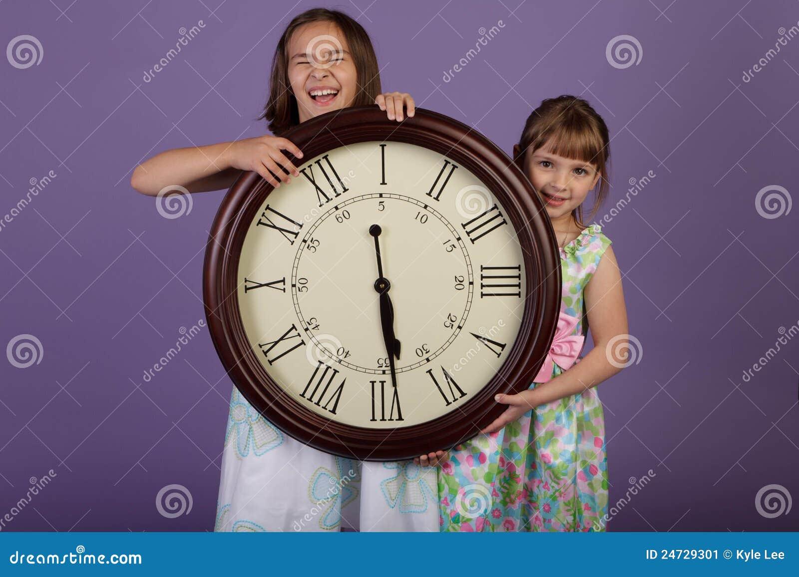 Dos muchachas de risa que sostienen un reloj de pared - Relojes pared grandes ...
