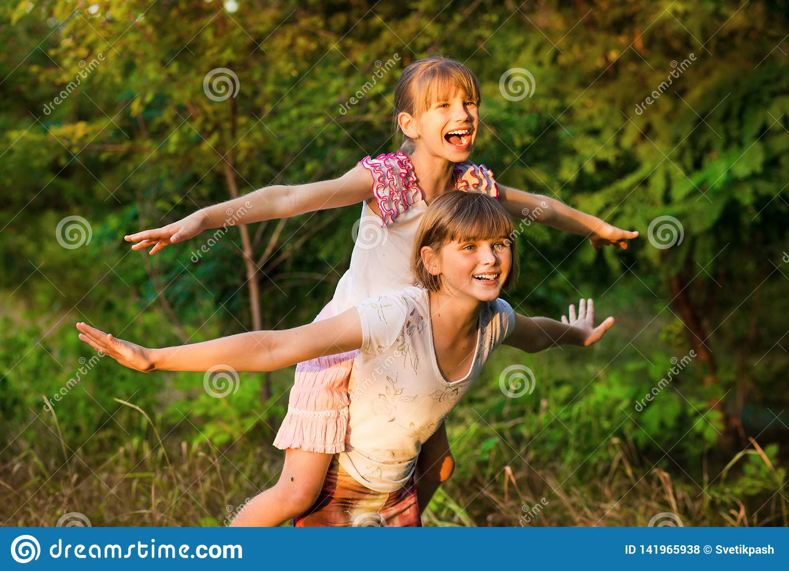 Dos muchachas del niño que juegan junto Las hermanas juegan al super héroe Niños felices que tienen la diversión, la sonrisa y ab