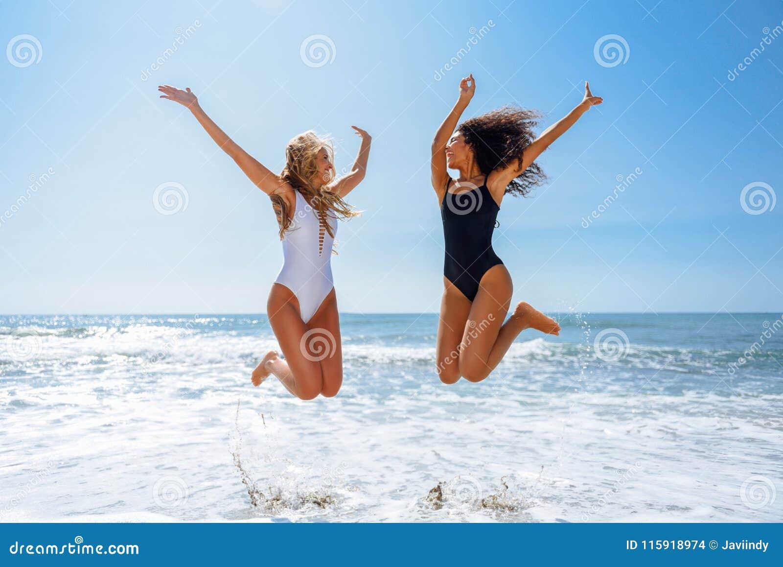Dos muchachas divertidas en el traje de baño que salta en una playa tropical